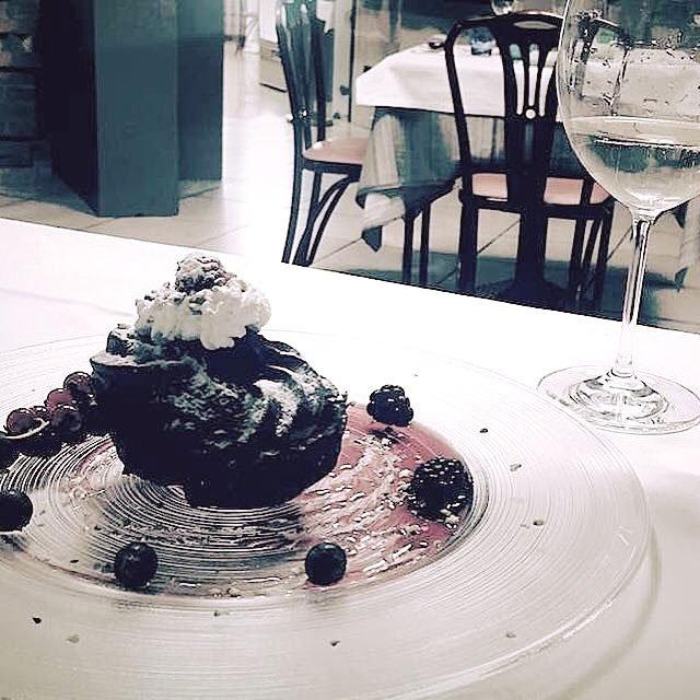 Torta nera con more, uva nera  e panna su un vassoio di vetro