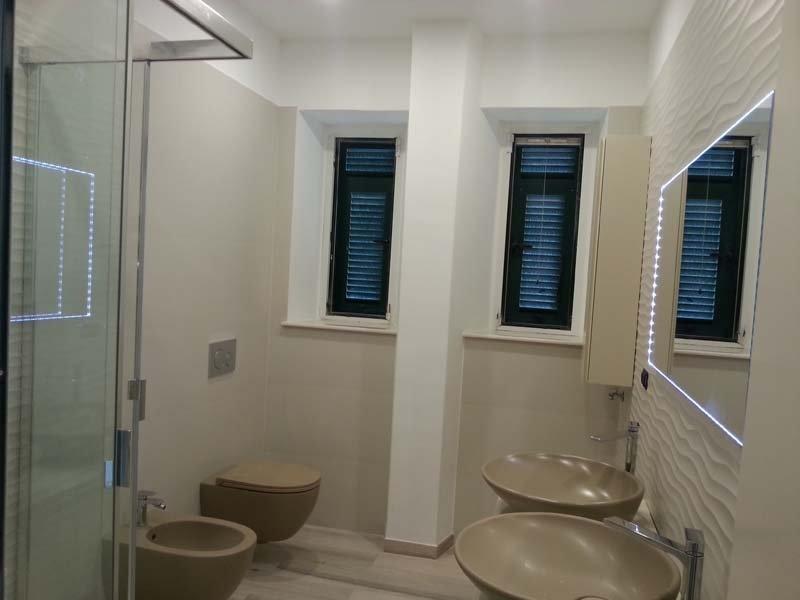 vista frontale di bagno moderno con box doccia in vetro, lavabi , specchio, bide e arredo da bagno