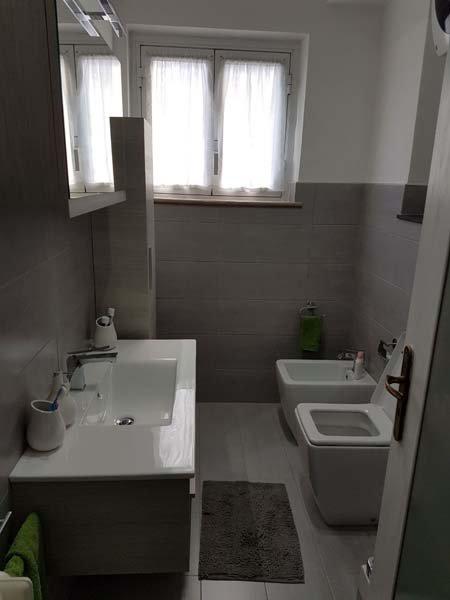 bagno moderno con lavabo, bide, asciugamani e finestra