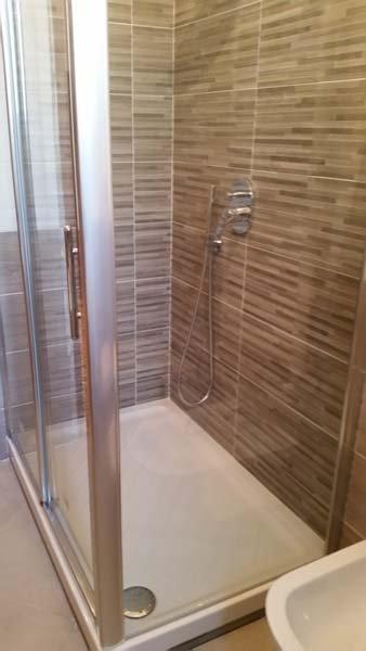 box doccia in vetro con parete decorata in un bagno moderno