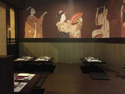 dei tavoli piccoli stile giapponese e un dipinto al muro raffigurante una geisha