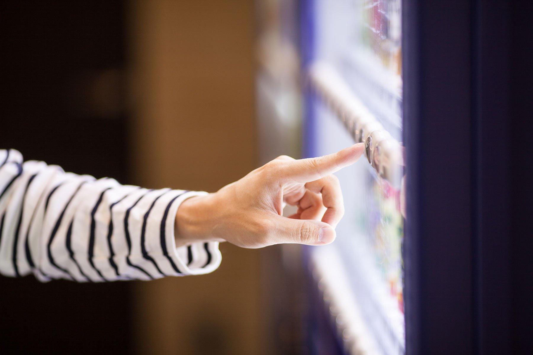 un dito che preme il pulsante di un distributore automatico