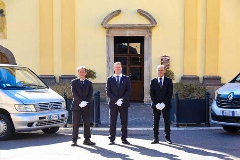 tre uomini dell'agenzia funebre davanti ad una chiesa
