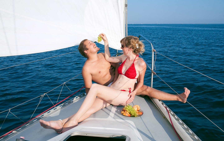 coppia seduta a prua mentre scherza e mangia frutta