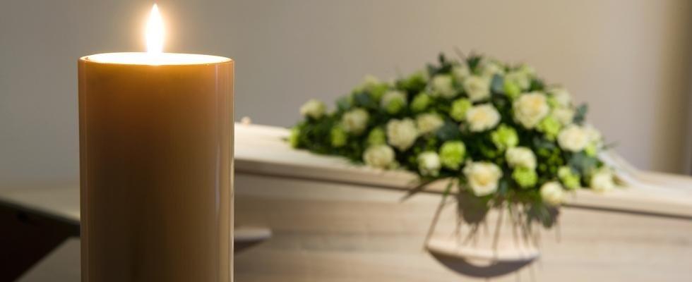 candela e bara funebre con fiori appoggiati sopra