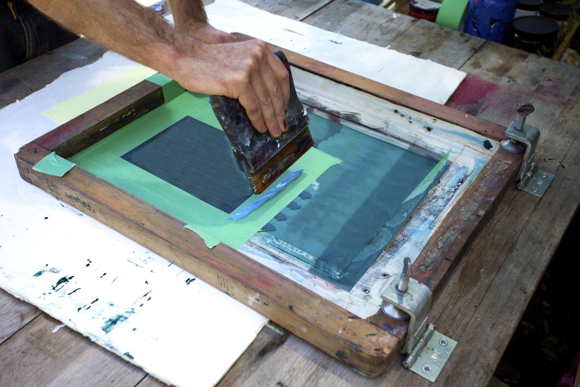 una maglietta verde e dietro l'interno di una fabbrica