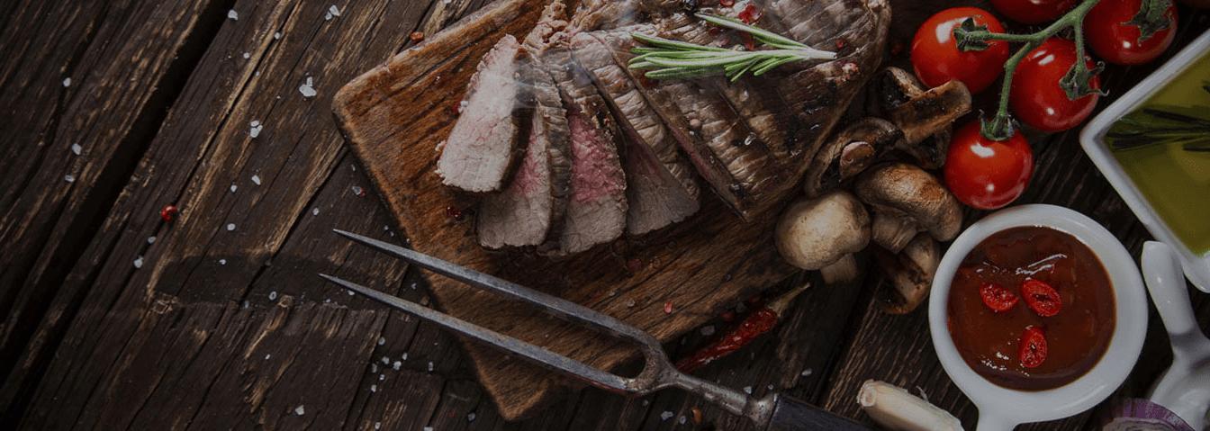 tagliere con carne alla griglia con funghi pomodori a grappolo e due salse