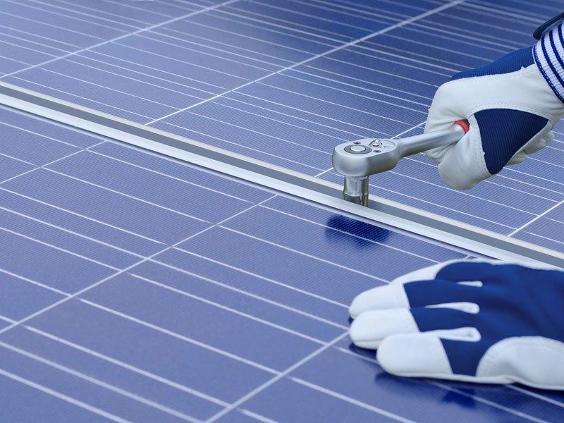 operaio con guanti che ripara un pannello solare