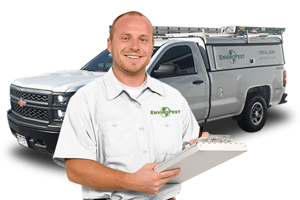 enviropest technician in front of service truck