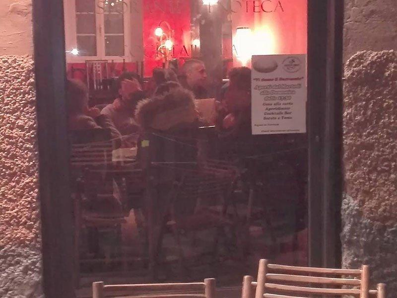 vista dall'esterno attraverso il vetro dell'interno del bar con delle persone in piedi