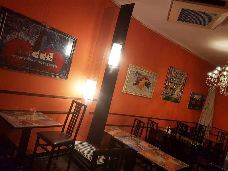 interno del bar con vista dei tavoli muri arancioni con dei quadri sulla parete e sulla destra si vede un lampadario