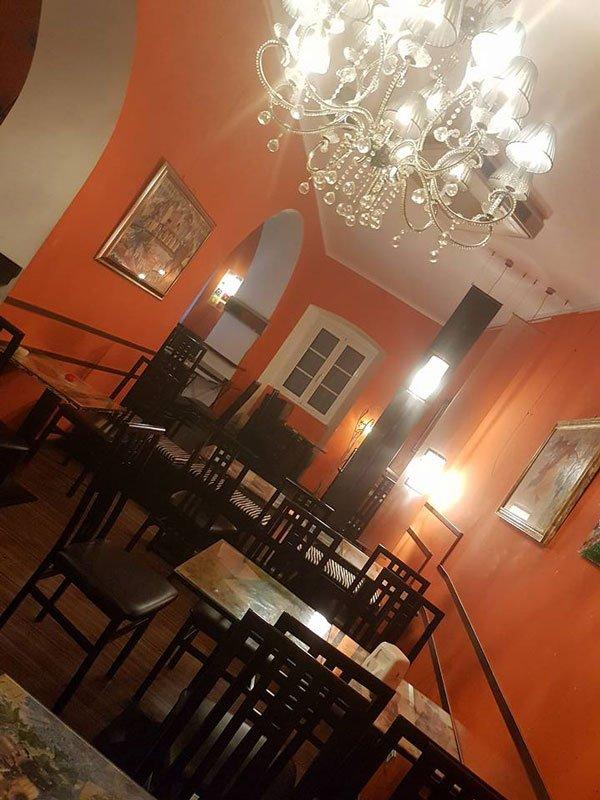 vista obliqua dell'interno del bar con muri arancioni e tavoli e sedie marroni scure