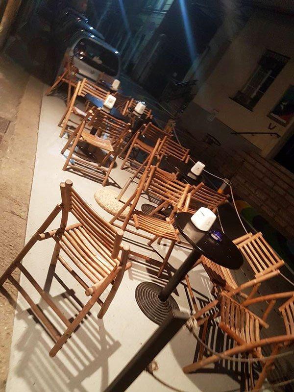 tavoli e sedie all'esterno del bar con alcune macchine parcheggiate