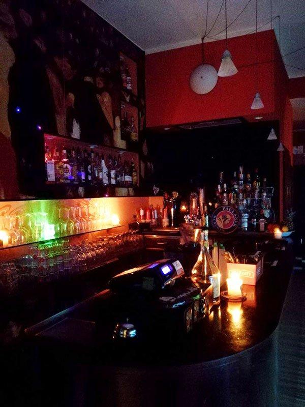 vista laterale del  bancone del bar illuminato con luci verdi e arancioni