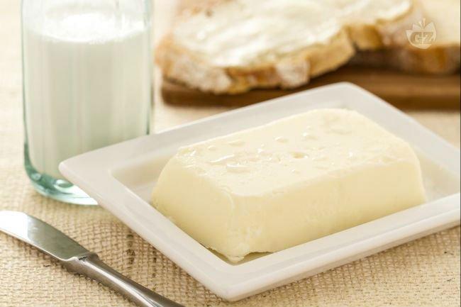 un vassoio di plastica con del burro e accanto un bicchiere di latte