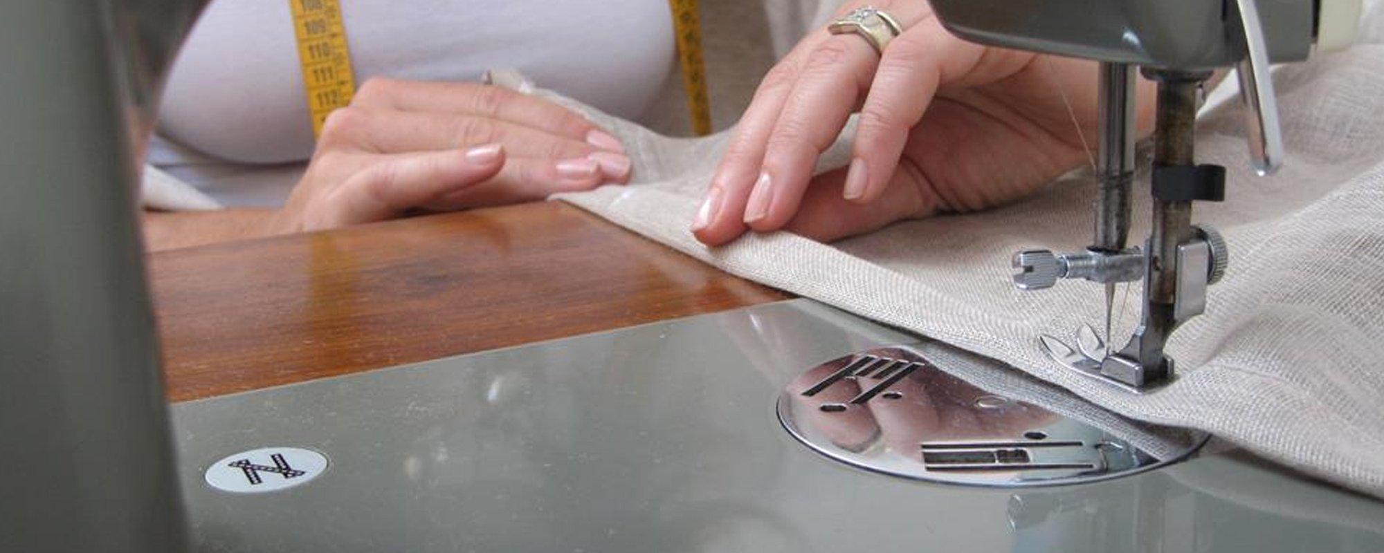 La sarta mentre cuce del tessuto in cotone