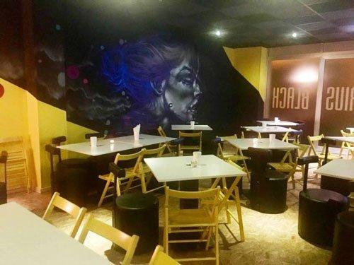 dei tavoli in legno in un pub e un dipinto blu al muro con un volto di una donna
