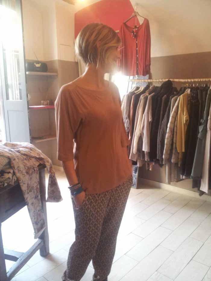 modella indossa un paio di pantaloni e una maglia arancione