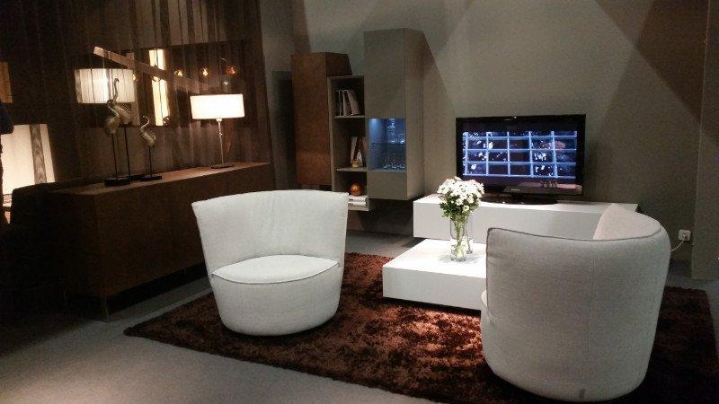 un salotto con due poltrone moderne color panna , un mobiletto tv