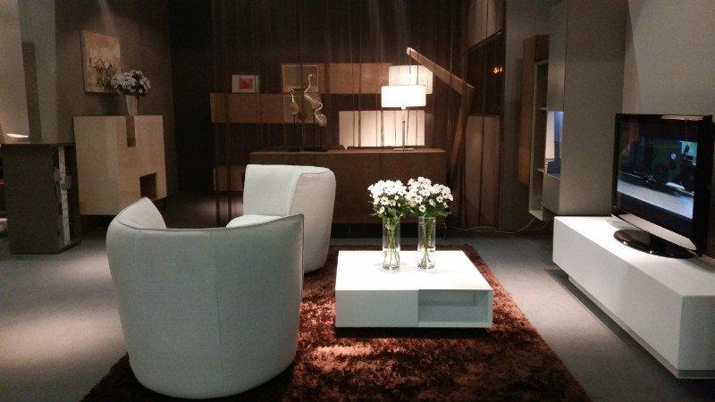 un salotto con due poltrone color panna moderne, un tavolino con due vasi di fiori bianchi e un mobiletto con sopra una tv