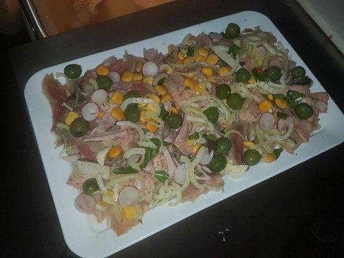 un piatto con mais, cipolle, carne,olive e finocchi