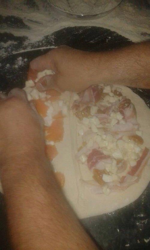 due mani che farciscono una pizza