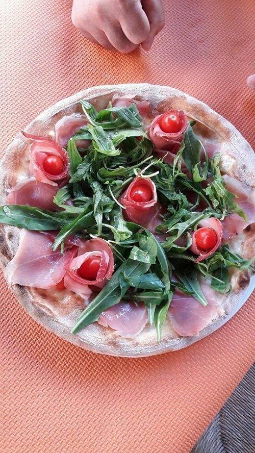 un piatto con rose di prosciutto,pomodorini e insalata