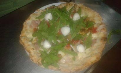 una pizza bianca con mozzarelline, prosciutto e rucola