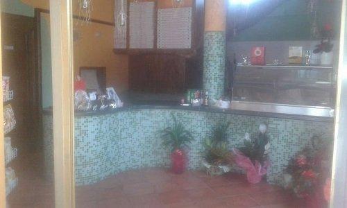 interno di una pizzeria con un bancone con piastrelle a  mosaico azzurre e nere