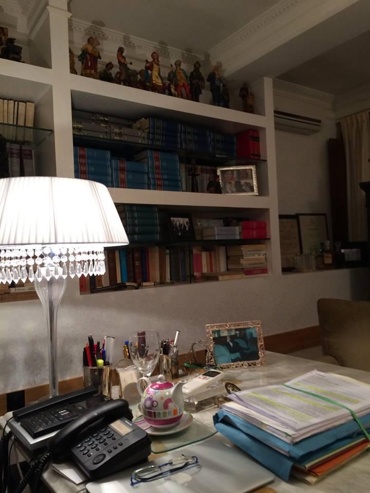 vista laterale di un ufficio con una libreria e oggetti sul tavolo
