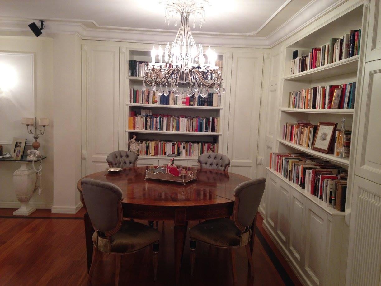 un ufficio con sedie, tavolo rotondo, pavimento in legno, lampadina in soffitto e delle librerie