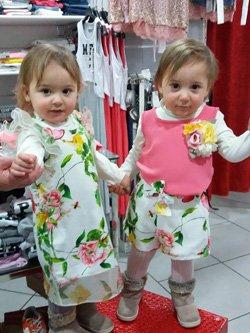 due bambine gemelle con due vestiti a fiori