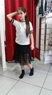 bambina con maglietta e gonna nera vicino a un camerino
