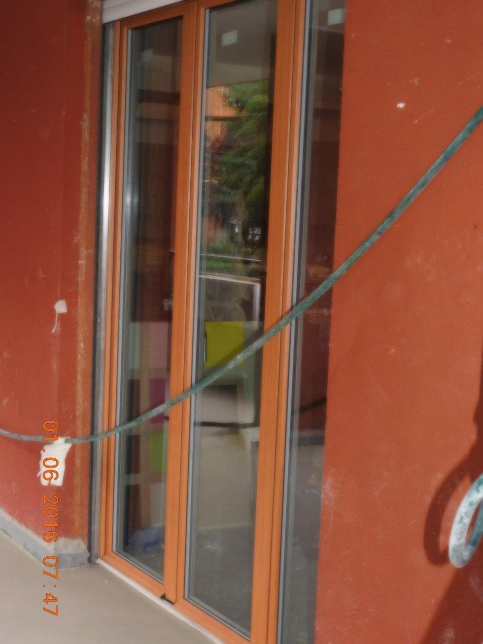 vista laterale di una finestra in legno con un filo elettrico che passa davanti al vetro