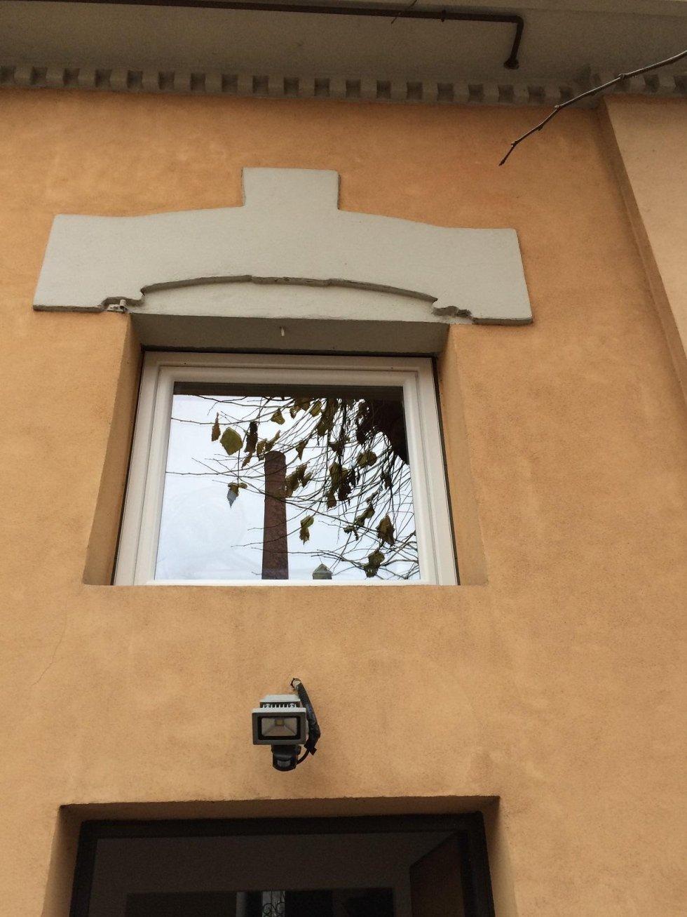 vista dal basso di una finestra con stucco decorativo nella parte superiore