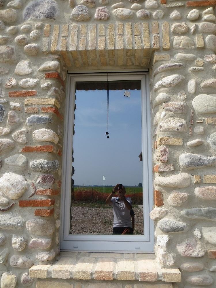 finestra in un muro di pietra con riflessa una persona che scatta una foto