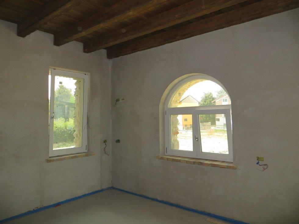 due finestre di forme diverse a vasistas vicino all`angolo di una stanza