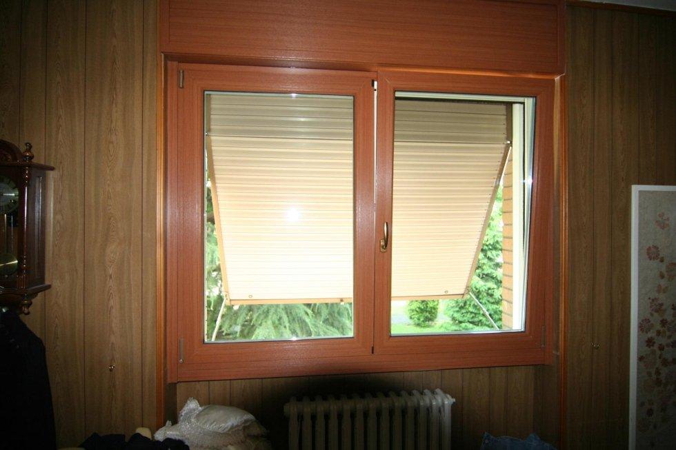 finestra in legno con vista su una tenda parasole aperta verticalmente