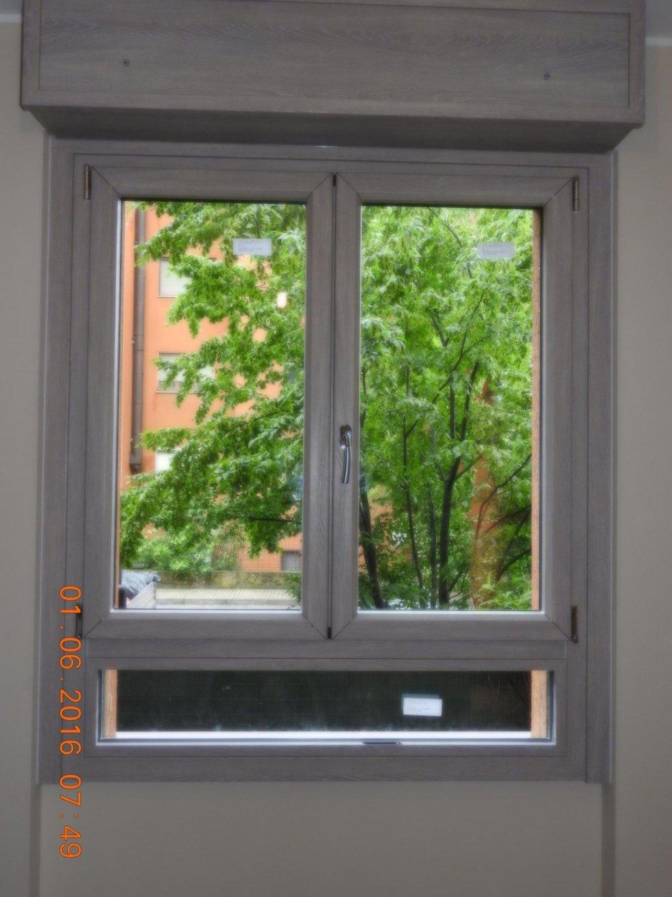 finestra in legno chiaro con vista su un albero