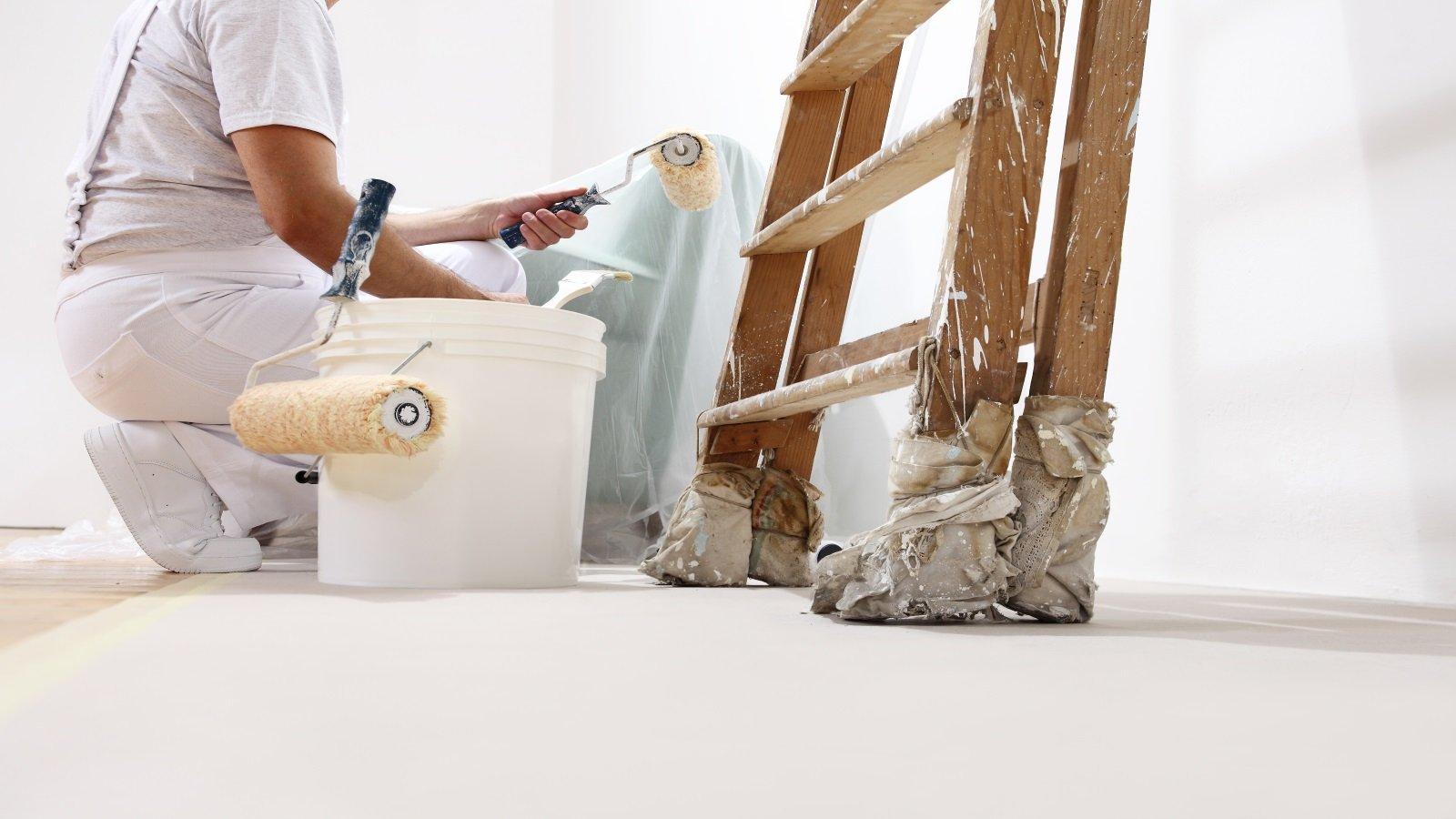 Pittore con rullo e pennello nelle mani accanto a una scala e un secchio di vernice bianco