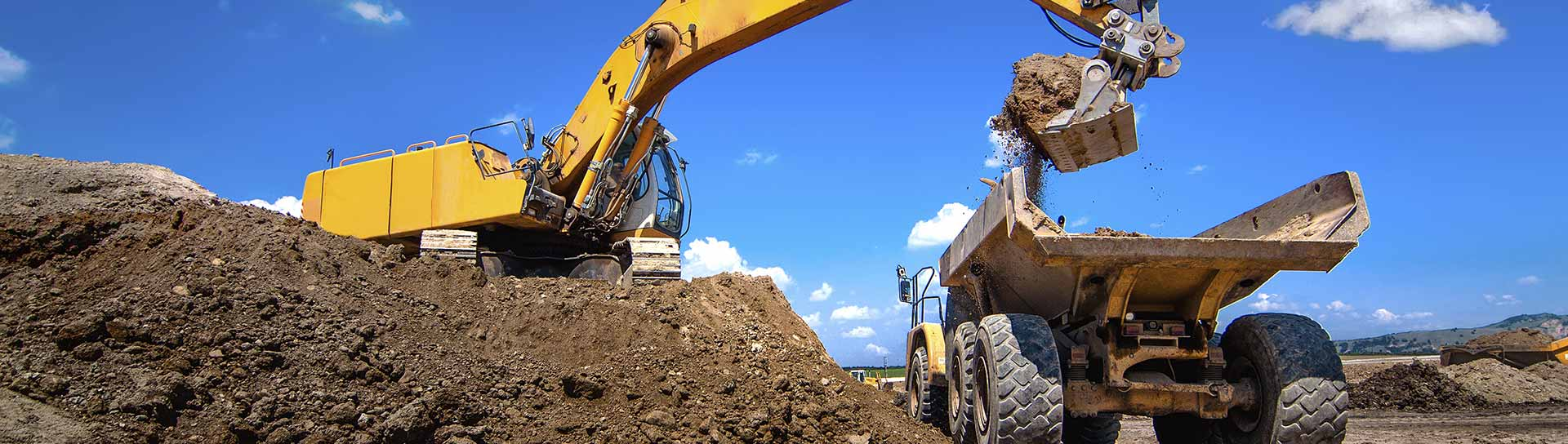 yellow excavator digging