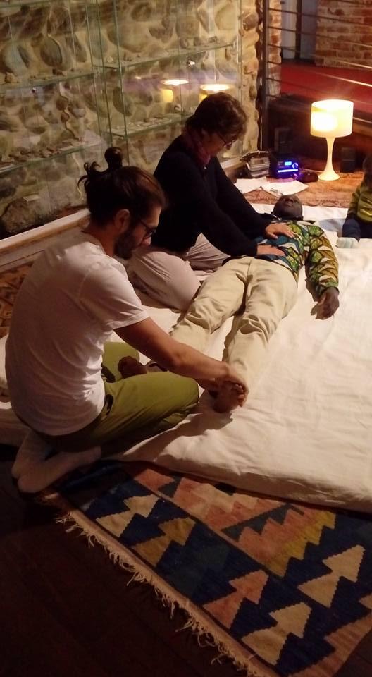 due persone massaggiano un uomo steso