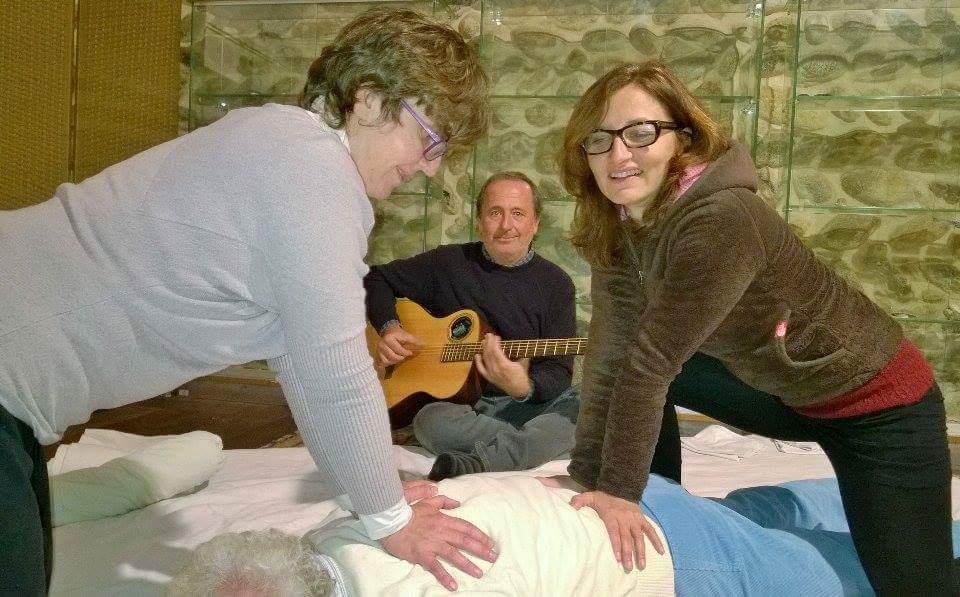 due donne massagigano un persona e un uomo suona la chitarra sullo sfondo