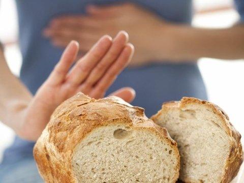 donna si tiene la pancia e allontana una pagnotta di pane
