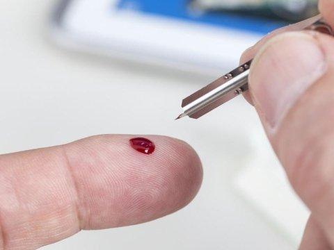 goccia di sangue sul dito di una persona durante un controllo glicemico
