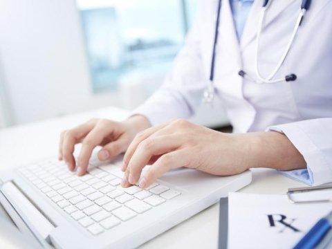 Dottore mentre lavora su un portatile