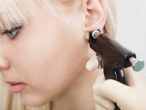 mano che fora un orecchio a una ragazza bionda