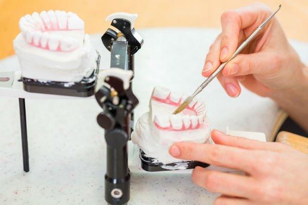 una mano che lavora su due protesi dentarie
