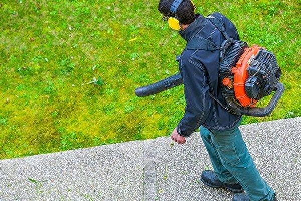 un giardiniere con delle cuffie mentre usa un soffiatore