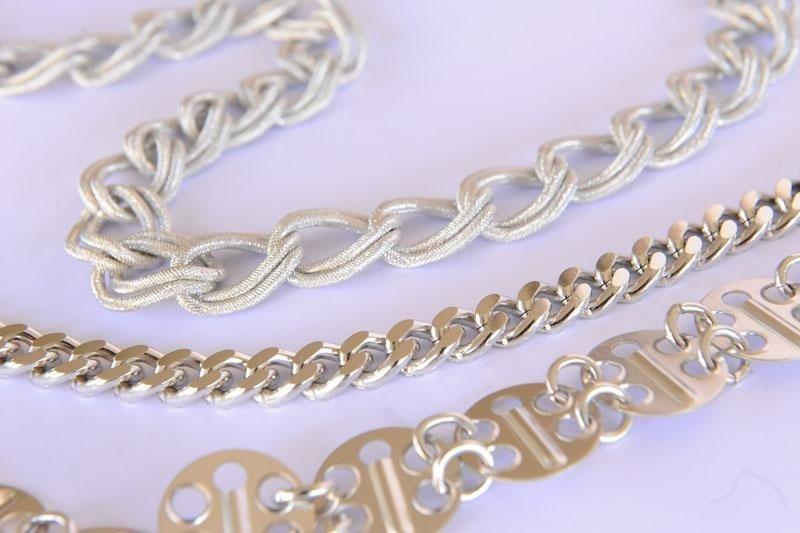 primo piano di tre diversi tipi di catene metalliche finto argento